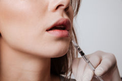 Cropped image of young woman make lip injections. Cropped image of young woman standing over gray background and make lip injections royalty free stock photography
