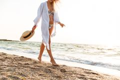 Cropped image of a young woman in summer clothes. Holding hat, walking along the beach Royalty Free Stock Photo
