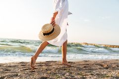 Cropped image of a young woman in summer clothes. Holding hat, walking along the beach Royalty Free Stock Photos