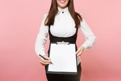 Cropped Joyful business woman giving pen for signature on clipboard tablet with blank empty sheet workspace copy space. On pink background. Lady boss stock photo