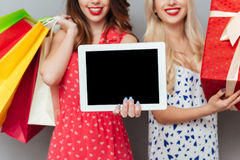 Cropped of ladies friends holding shopping bags showing tablet display. Stock Photos