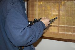 Cropped man in hoodie jacket holding an air rifle standing by a window with the woods outside showing through woven shade.  stock images