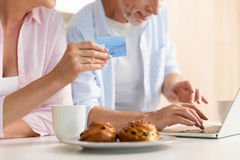Cropped of mature loving couple using laptop holding credit card. Cropped photo of mature loving couple family standing at the kitchen using laptop computer Royalty Free Stock Image