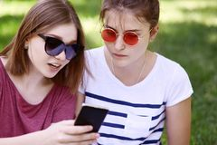 Cropped outdoor shot of two female best friends in trendy shades, dressed casually, read information via smart phone in internet, royalty free stock images