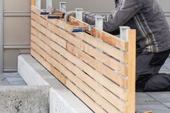 Unrecognizable man repairing new wooden fence near house. Cropped photo of adult handyman or workman repairing new wooden fence near house using c-clamp stock images