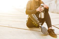 Cropped photo of athletic disabled girl with prosthetic leg in s. Portswear sitting on concrete floor outdoors and holding thermos cup royalty free stock photo