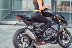 A beautiful biker girl sitting on her superbike outside a glass building. Cropped photo of a beautiful biker girl sitting on her superbike outside a glass stock images