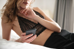 Cropped photo of beautiful sexy brunette woman lies on bed. Dressed in lingerie chatting by phone Royalty Free Stock Image