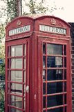 A cropped photo of a british telephone booth with an applied vintage filter. A cropped photo of a british red unused telephone booth with an applied vintage Royalty Free Stock Photography