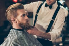 Cropped photo of a classy dressed barber shop stylist working for a perfect look of a red bearded guy in a cape. His hairdo looks royalty free stock photography