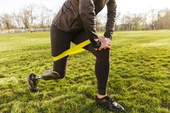 Cropped photo of disabled girl in tracksuit, exercising and doing lunges with prosthetic leg on grass using resistance band. Cropped photo of disabled girl in royalty free stock image
