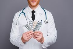 Cropped photo of doc hands hold pills packs isolated on dark gra. Y background stand in white wear stock photography