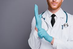 Cropped photo of doc puts blue glove on hand isolated on dark gr. Ay background with copy space for text stand in white wear royalty free stock photography