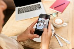 Cropped photo of european woman wearing hat photographing food on mobile phone royalty free stock image