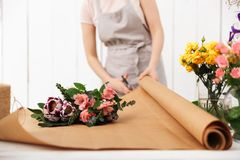 Cropped photo of florist woman working. Cropped photo of florist woman standing near table working with flowers in workshop Royalty Free Stock Image