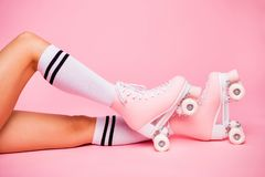 Cropped photo of girls foot wearing four -wheeled equipment quads lying isolated over pink background