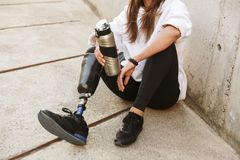 Cropped photo of handicapped woman having bionic leg in streetwear, sitting on concrete floor outdoor and holding thermos cup. Cropped photo of handicapped woman stock images
