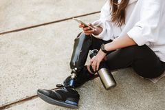 Cropped photo of handicapped woman in streetwear having bionic l. Eg sitting on concrete floor outdoor and using cell phone stock photos
