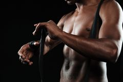 Cropped photo of the hands young afroamerican boxer, winds boxin. G bandages, over black background Royalty Free Stock Image