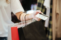 Cropped photo of lady with shopping bags holding debit card. Stock Image