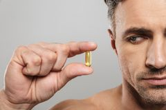 Cropped photo of of mature man holding pill. Cropped photo of of mature man standing isolated over grey wall background naked holding pill royalty free stock images