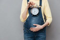 Cropped photo of pregnant woman holding clock Stock Photography