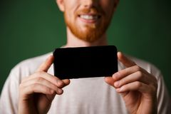 Cropped photo redhead bearded man in white tshirt makes a photo stock photography