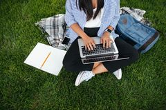 Cropped photo of student girl in casual wear, using laptop, sitt Stock Images
