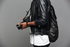 Cropped photo of stylish african man with backpack holding photo stock photos