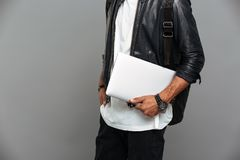 Cropped photo of stylish african man in leather jacket holding l. Aptop, isolated on gray backgroung Stock Photo