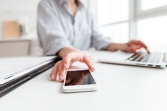 Cropped photo of woman in shirt holding smartphone while sitting royalty free stock image