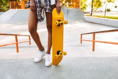 Cropped photo of young african woman with skateboard. Stock Images