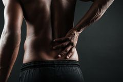 Cropped photo of young afro american man with back pain. Over black background Stock Images