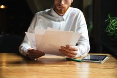 Cropped photo of young readhead bearded man working with papers. And tablet computer Royalty Free Stock Images