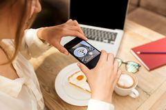 Cropped photo of young woman wearing hat photographing food on cell phone royalty free stock photography
