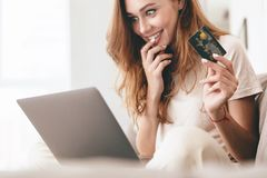 Cropped picture of lady using laptop computer holding credit card. Cropped picture of young happy amazing pretty lady sitting on sofa indoors. Looking aside Stock Photos