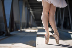 Cropped picture legs of graceful ballerina in. White tutu in the industrial background of the bridge Stock Image