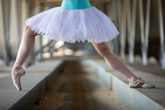 Cropped picture legs of graceful ballerina in. White tutu in the industrial background of the bridge Stock Photo