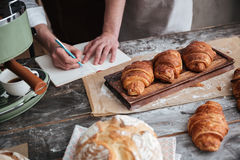 Cropped picture of man baker writing notes. At notebook standing at bakery Royalty Free Stock Image
