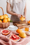 Cropped picture of woman squeezes out juice of a citruses. Stock Photo