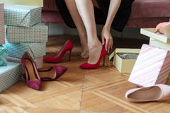 Cropped picture of young lady choosing shoes. Stock Photo