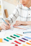 Cropped picture of young woman fashion illustrator drawing. Cropped picture of young woman fashion illustrator sitting at the table and drawing Stock Photo