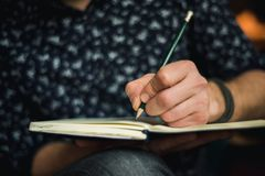 Man writing in journal with a pencil. Cropped pictures of a man making notes, writing in his journal Stock Photos