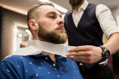 Barber putting hairdresser tape around customer neck. Cropped portrait of barber putting hairdresser tape around customer neck Royalty Free Stock Photo