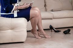 Cropped portrait bottom view woman`s legs wearing blue and white dress black high heel shoes sitting on white armchair touching stock photography