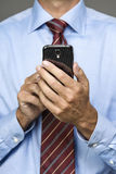 Cropped portrait of businessman on mobile phone. Cropped image of businessman on smart phone Stock Image