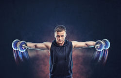 Cropped portrait of a fitness man doing lateral raise with dumbbells stock image