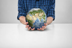 Cropped portrait of a man sitting with Earth in his hands Royalty Free Stock Photo