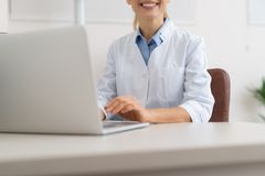 Joyful doctor in white lab coat using notebook at work royalty free stock photo