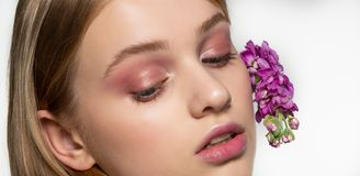 Cropped portrait of young girl with closed eyes, bright makeup, purple flowers curled in hair. Health and natural beauty stock photography